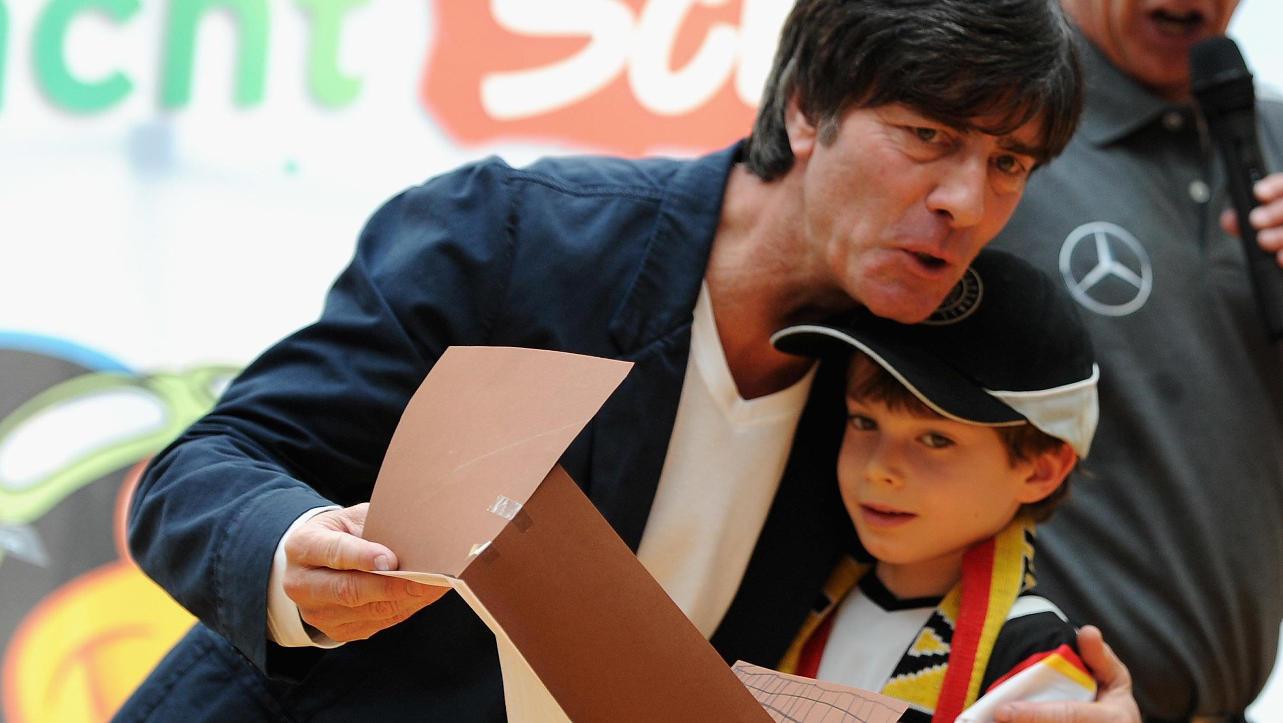 Bundestrainer Joachim Loew umarmt einen junge Fußballfan während eines Schulbesuchs. (Photo by Dennis Grombkowski/Bongarts/Getty Images)
