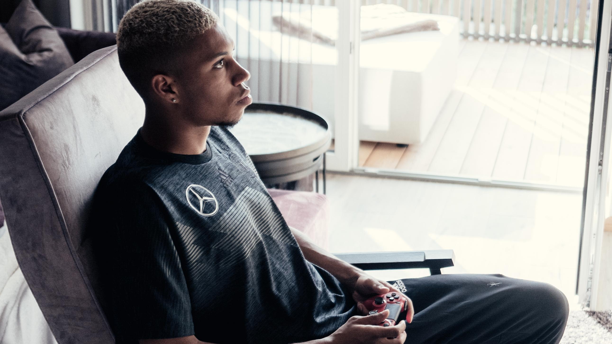 Ein Spieler der deutschen Nationalmannschaft sitzt auf einem Sessel und spielt ein Videospiel.