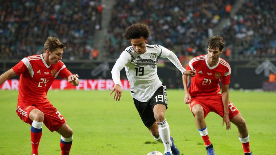 Leroy Sané ist zu sehen wie er im Dress der deutschen Nationalmannschaft einen Zweikampf gegen zwei Gegenspieler führt. Er bleibt dabei im Ballbesitz.