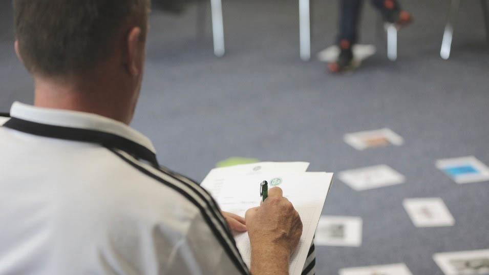 Ein Teilnehmer des DFB-Ausbilderzertifikats im Modul Methodenkompetenz schreibt etwas auf.