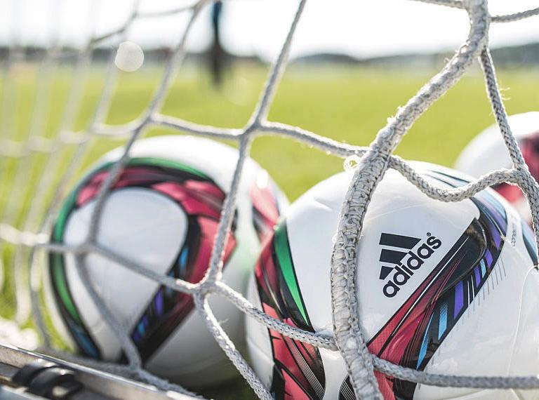 Auf einem Fußballfeld liegen drei Fußbälle in einem Tornetz.