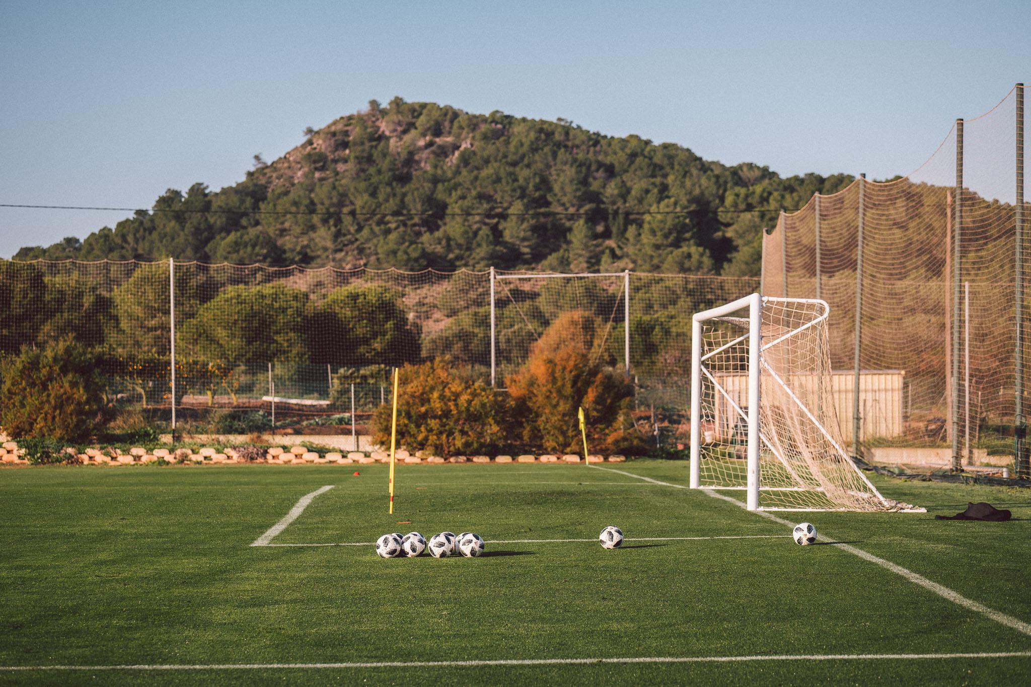 Ein seitliche Aufnahme eines Fußballtores, vor dem viele Bälle liegen.