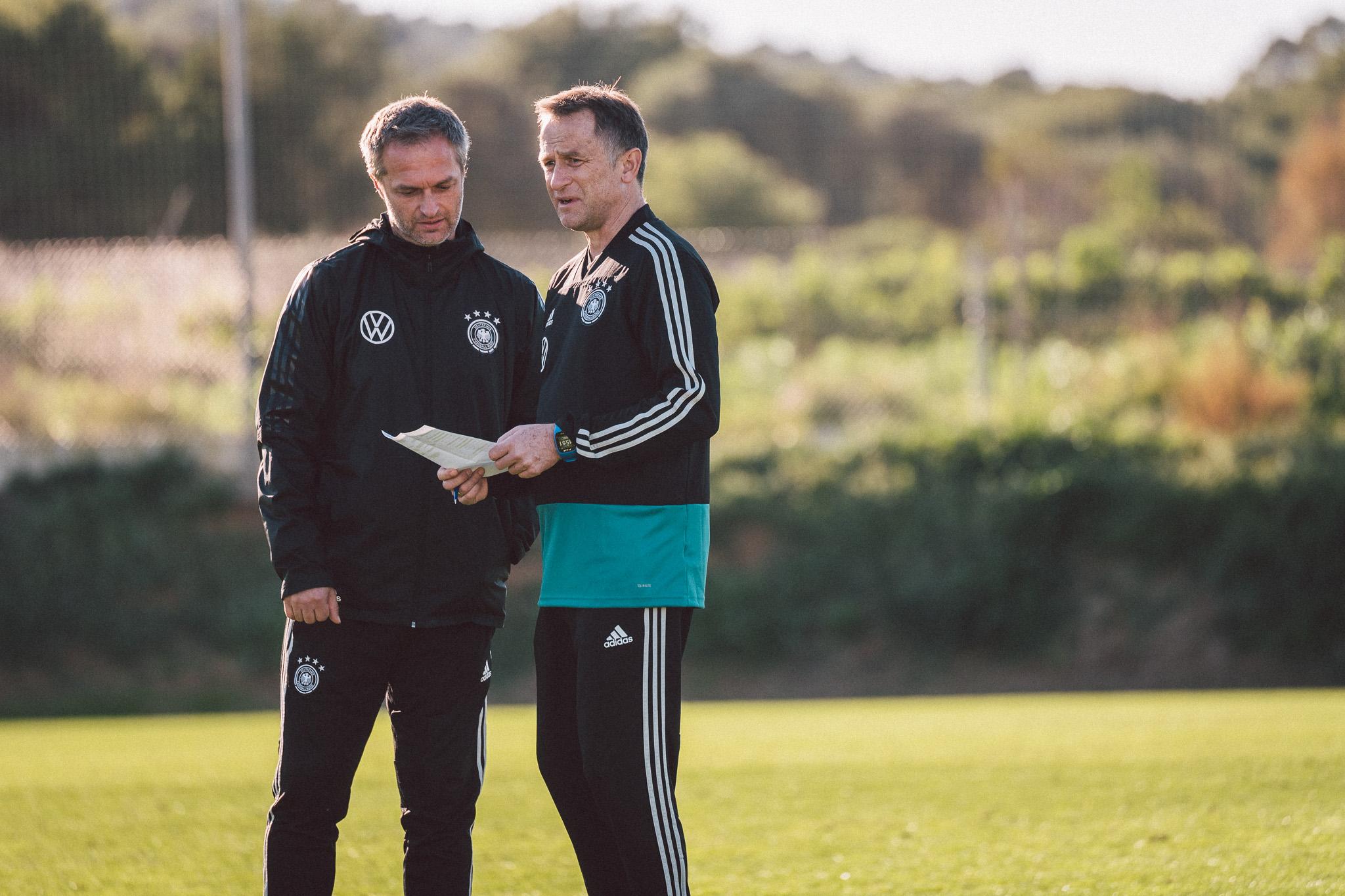 Zwei Trainer besprechen sich vor dem Training auf dem Platz. Einer hält einen Notizzettel in den Händen.